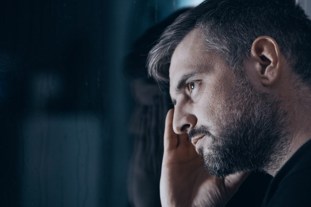 man struggling with withdrawal symptoms looking through glass