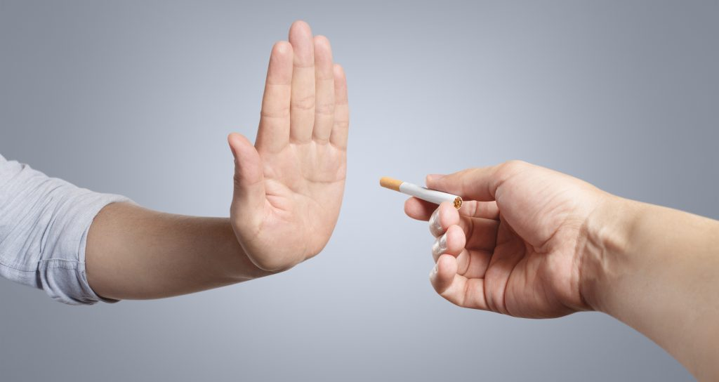 Hand refusing a cigarette offer on grey background