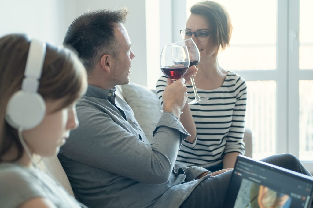 Child in headphones ignoring parents drinking wine