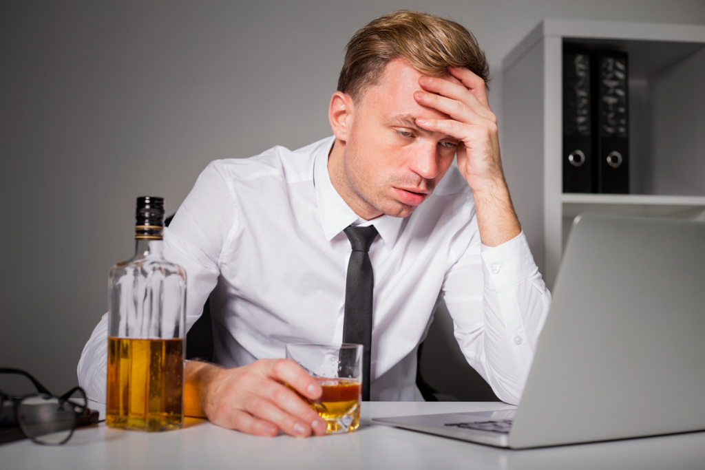 Alcoholic at computer with a whisky in his hand